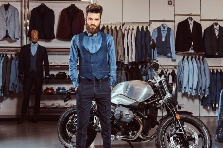 Photo for Elegantly dressed man with stylish beard and hair posing with hands in pockets near retro sports motorbike at the mens clothing store. - Royalty Free Image