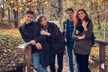Group of young friends hiking in autumn colorful forest.
