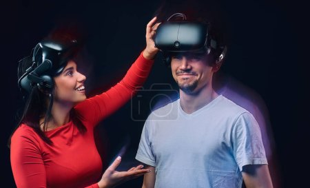 Young joyful girl adjusts virtual reality glasses on her boyfriend. Couple gamers with VR headsets.