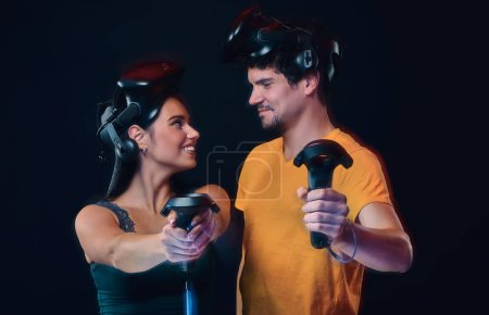 Happy young couple of gamers posing with virtual reality goggles and controllers. Isolated on dark background.