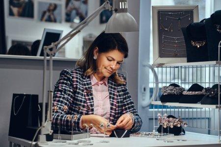 Photo pour Portrait de femme élégamment habillée vendeur emballe des boucles d'oreilles précieuses dans une boîte pour son client dans une bijouterie de luxe . - image libre de droit