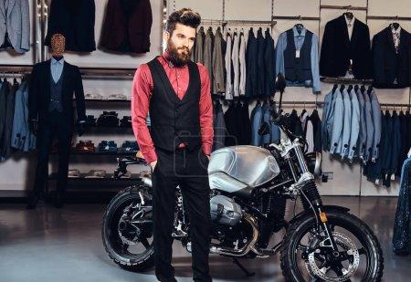 elegant gekleideter Mann posiert mit Händen in Taschen in der Nähe von Retro-Sportmotorrädern im Herrenbekleidungsgeschäft.