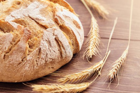 Freshly baked bread and spikelets of wheat.