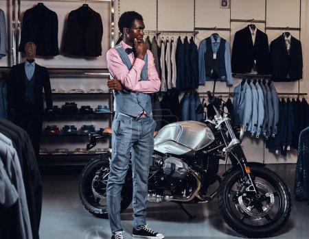 elegant gekleideter afrikanisch-amerikanischer junger Mann posiert in der Nähe von Retro-Sportmotorrädern im Herrenbekleidungsgeschäft.