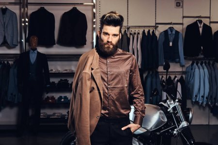 Elegantly dressed man with stylish beard and hair posing near retro sports motorbike at the mens clothing store.