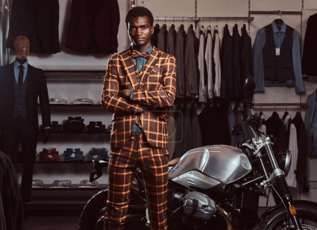 Photo for Stylish African-American man dressed in a trendy elegant suit posing with crossed arms near retro sports motorbike at the mens clothing store. - Royalty Free Image
