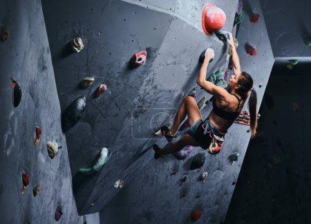 Photo pour Jeune femme sportive escalade rocher artificiel à l'intérieur . - image libre de droit