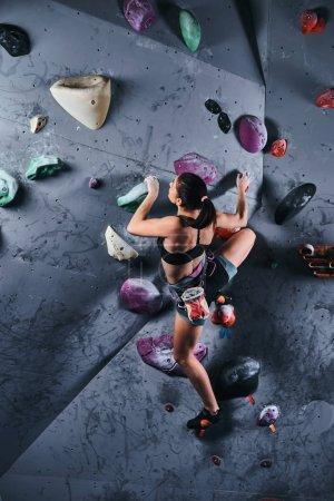 Photo pour Vue arrière d'une femme grimpeuse sportive professionnelle s'entraînant sur un mur intérieur . - image libre de droit