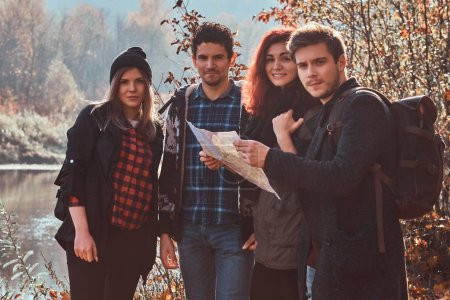 Photo for Travel, hiking, adventure concept. Group of young friends hiking in autumn colorful forest, looking at map and planning hike. - Royalty Free Image