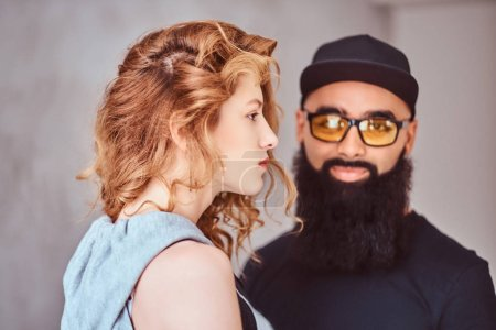 Photo for Attractive stylish couple. Portrait of an Arabian bearded male and beautiful redhead girl. - Royalty Free Image