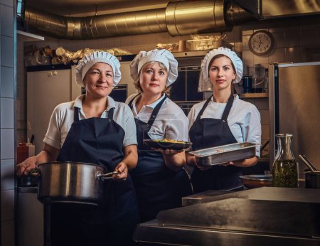 Happy cooking team wearing a uniform holding conta...