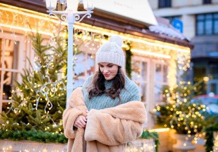 Foto de Hermosa chica vestida con un sombrero de invierno y piel capa pie tarde calle decorado con hermosas luces en Navidad - Imagen libre de derechos