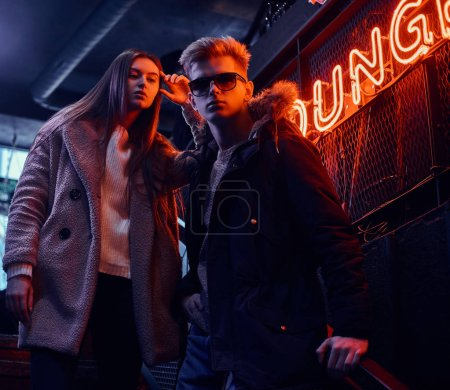 Photo for Trendy dressed young couple standing on stairs to the underground nightclub, a backlit signboard in the background - Royalty Free Image