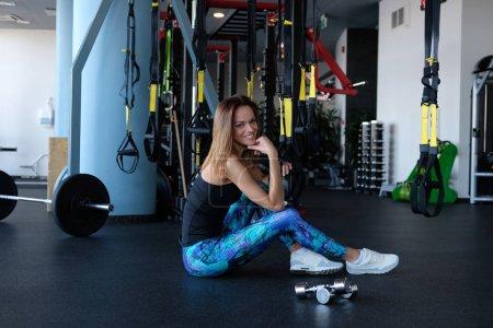 Photo pour Joyeux mince fille de remise en forme assis sur un sol dans la salle de gym - image libre de droit