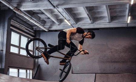 Jeune homme avec BMX effectuer des tours dans le skatepark à l'intérieur