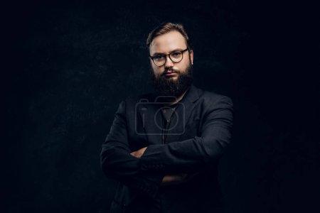 Photo pour Portrait d'un hipster croisé les bras dans un studio sur fond noir - image libre de droit