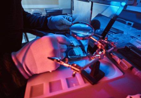 Photo pour Le technicien répare une tablette cassée dans un atelier de réparation moderne. Illumination avec des lumières rouges et bleues - image libre de droit