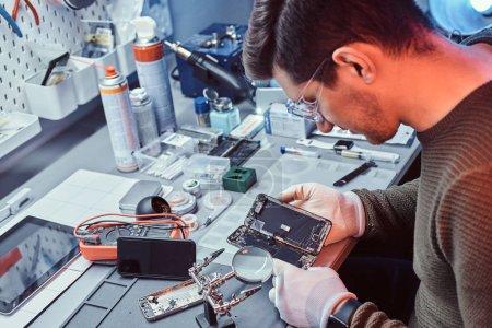 Photo pour Le technicien examine attentivement l'intégrité des éléments internes du smartphone dans un atelier de réparation moderne - image libre de droit