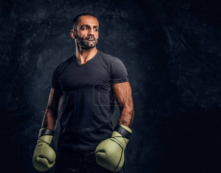 Portrait of a brutal professional fighter in a black shirt and gloves. Studio photo against a dark textured wall