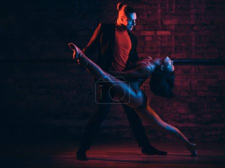 Photo for Professional dancers perform an incendiary dance in a dark room with illumination - Royalty Free Image