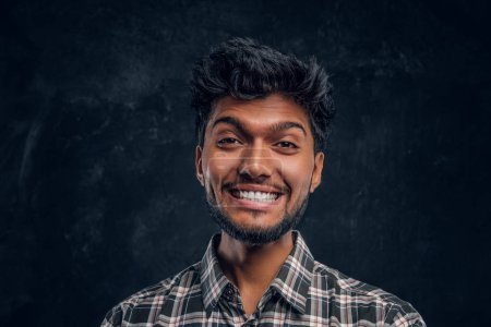 Close-up portrait of a handsome Indian man wearing a plaid shirt, smiling and looking at a camera.