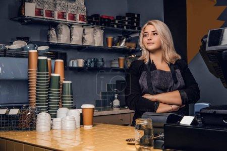Photo pour Barista femme confiante posant avec les bras croisés et regardant de côté dans un café ou un café - image libre de droit