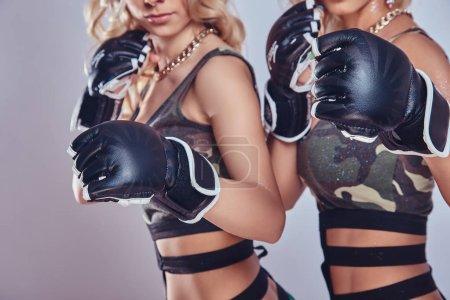 Photo pour Image recadrée d'une fille sexy portant des gants de combat. posant pour une caméra - image libre de droit