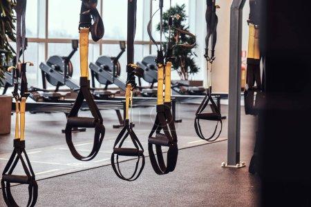 Photo pour Intérieur et équipement dans la salle de gym moderne, vue rapprochée des bretelles de suspension. Sport, fitness, santé . - image libre de droit