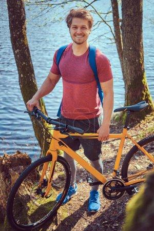 Photo pour Portrait d'un bel homme souriant en tenue de sport avec un vélo. Détente au bord du lac dans les bois . - image libre de droit