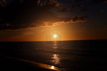 Photo for Dark sunset in with sun, sea, clouds and orange tones. - Royalty Free Image