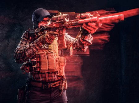 Photo for Special forces soldier wearing a checkered shirt and protective equipment holding an assault rifle and aim at the enemy. Red light effect in motion. Studio photo against a dark textured wall - Royalty Free Image