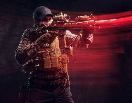 Special forces soldier wearing a checkered shirt and protective equipment holding an assault rifle and aim at the enemy. Red light effect in motion.