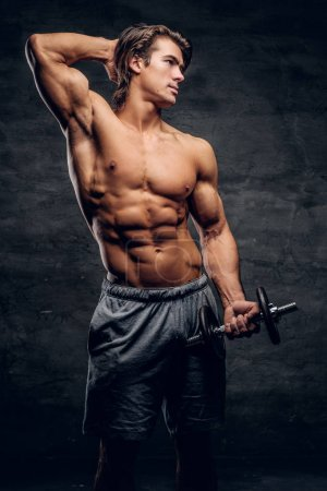 Photo for Beautiful young bodybuilder is posing with dumbbell. He has naked torso. - Royalty Free Image