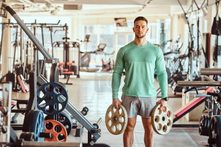 Photo for Sportive attractive man in green training shirt is doing his exsercises in gym with weights. - Royalty Free Image