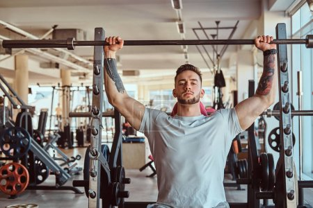 Photo for Young tattooed bodybuilder is doing his workout with barbell in gym. There are many sport equipment around. - Royalty Free Image