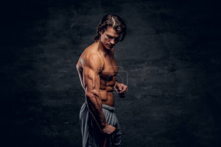 Photo for Attractive shirtless bodybuilder is posing with rubber and showing his muscules. - Royalty Free Image