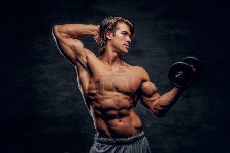 Photo pour Beau jeune bodybuilder pose avec haltère. Il a le torse nu. . - image libre de droit