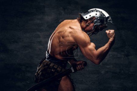 Photo for Strong shirtless gladiator in helmet is showing his muscules. He is wearing bandage. - Royalty Free Image
