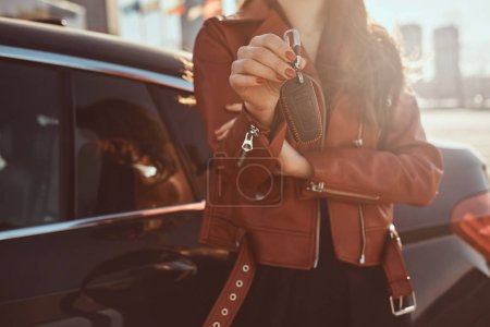 Photo pour Women in red leather jacket just sold her car, which is behide her. She holds key. There are sunny day. - image libre de droit