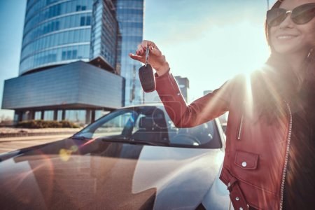 Photo pour Jeune femme heureuse vient d'obtenir les clés de sa nouvelle voiture, qui est behide. Il y a une belle journée ensoleillée. La femme porte la veste rouge et les lunettes de soleil. - image libre de droit