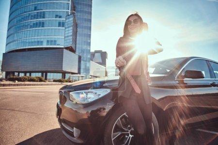 Photo pour Femme souriante heureuse retenant la clef pour la voiture, qui est la ci-cache, comme ceci est le cadeau pour quelqu'un. Elle porte une veste rouge et des lunettes de soleil. il ya le soleil se cacher son. - image libre de droit