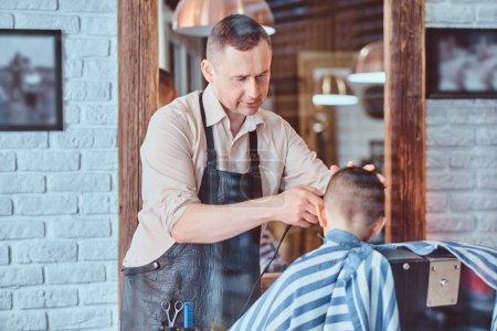Photo pour Petit garçon drôle se prépare pour l'école au salon de coiffure à la mode avec coiffeur mature . - image libre de droit