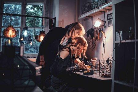 Photo pour Maître expiré et son nouvel assistant travaillent ensemble à faire une nouvelle lampe . - image libre de droit