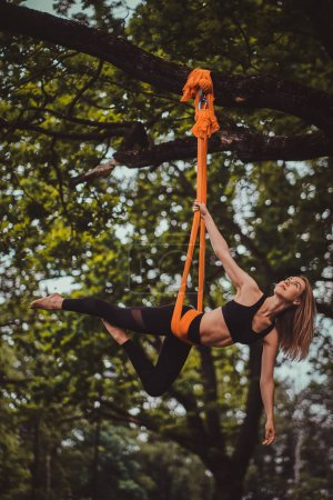 Photo for Beautiful pensive girl with long hair is doing exercises on sling in the summer forest. - Royalty Free Image