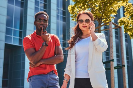 Photo for Serious bisness partners in sunglasses meeteng up near glass building at city centre. - Royalty Free Image