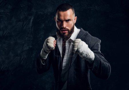 Photo pour Homme d'affaires barbu en colère en costume et gants de kickboxing protecteurs pose pour photographe au studio photo sombre . - image libre de droit
