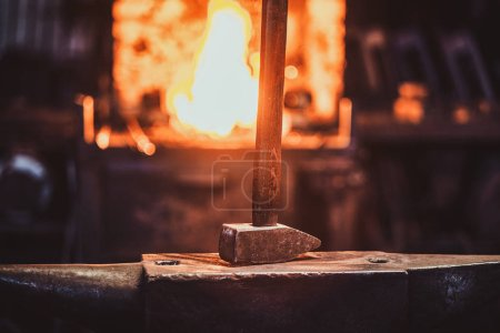 Photo for Hammer on anvil at dark blacksmith workshop with fire in stove at background. - Royalty Free Image