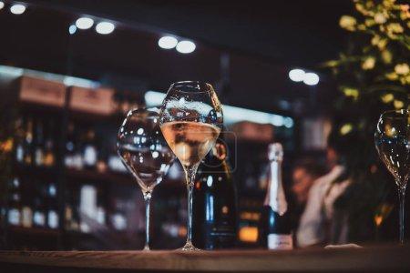 Photo pour Verres à vin sur la table du bar, un verre est vide, mais le second est rempli de vin blanc . - image libre de droit