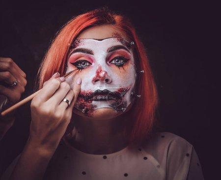 Photo pour Une maquilleuse talentueuse crée un art de l'Halloween particulièrement effrayant pour les femmes. - image libre de droit