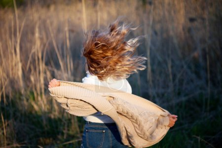 Photo for Girl is running out. Young woman in the field, feel freedom and happiness. Casual style. Back view - Royalty Free Image